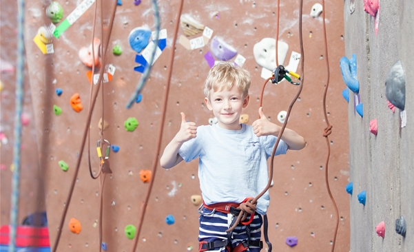 Child giving the thumbs up in a climbing harness