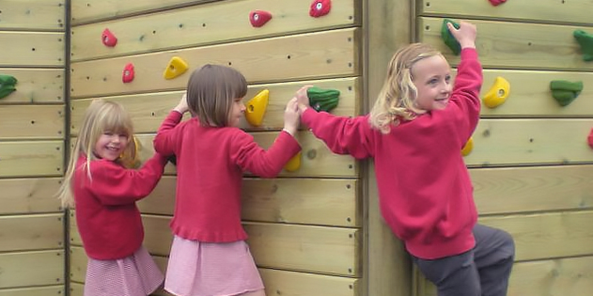 School girls climbing a zig zag wall