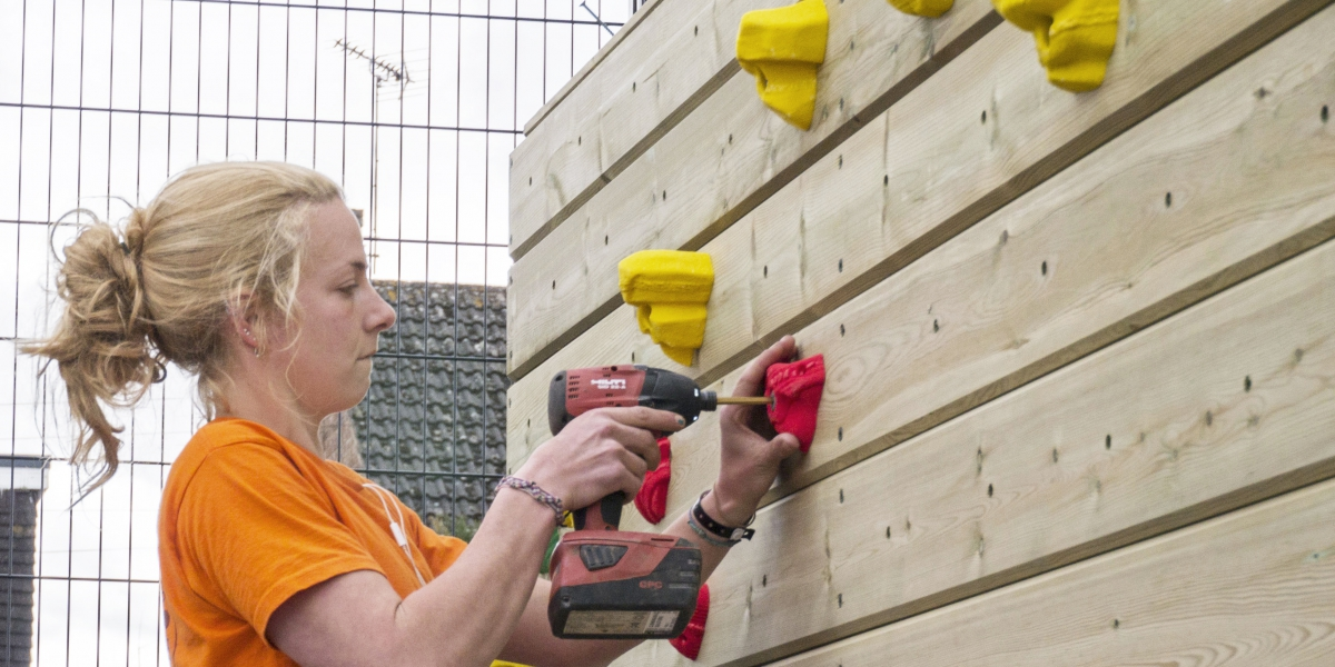 woman setting up a climbing wall with dril